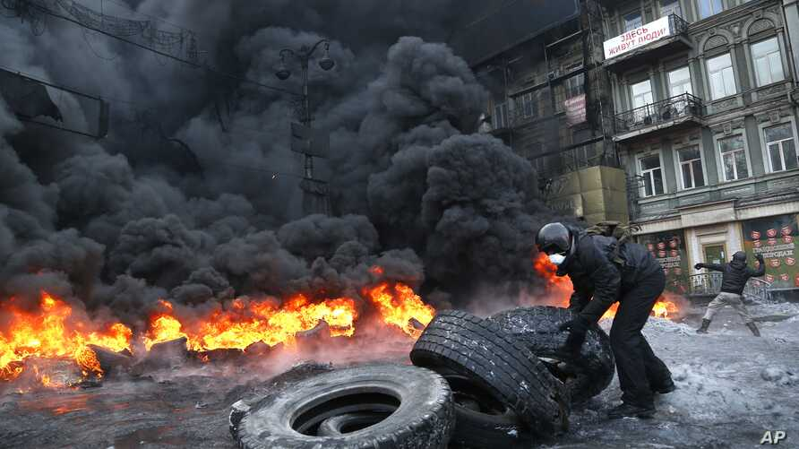 A protester prepares to throw a tire onto a fire during clashes with police in central Kiev, Ukraine, Jan. 25, 2014.