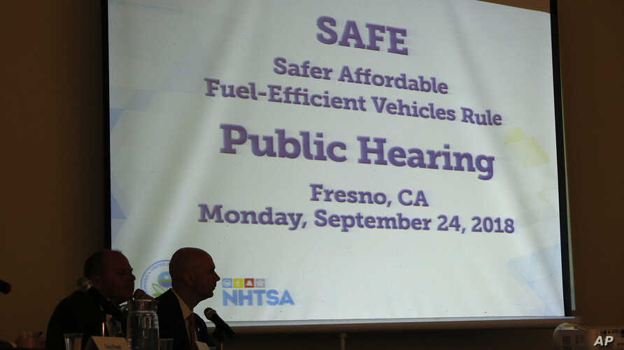 FILE - Mike Stoker, regional administrator of the US EPA and Jonathan Morrison of NHTSA listen to speakers during the first of three public hearings on the Trump administration's proposal to roll back car-mileage standards in a region with some of th