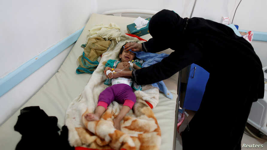 FILE  - A woman helps her son as he lies on a bed at a cholera treatment center in Sanaa, Yemen June 6, 2017. Picture taken June 6, 2017.