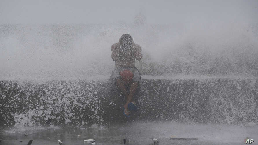 A Filipino reacts as he is hit by waves along a promenade in Manila, Philippines, Sept. 14, 2014.