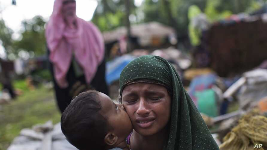 A Rohingya Muslim child kisses his mother's cheek as they rest after having crossed from Myanmar to the Bangladesh side of the border near Cox's Bazar's Teknaf area, Sept. 2, 2017. Tens of thousands have crossed into Bangladesh in the last 24 hours a