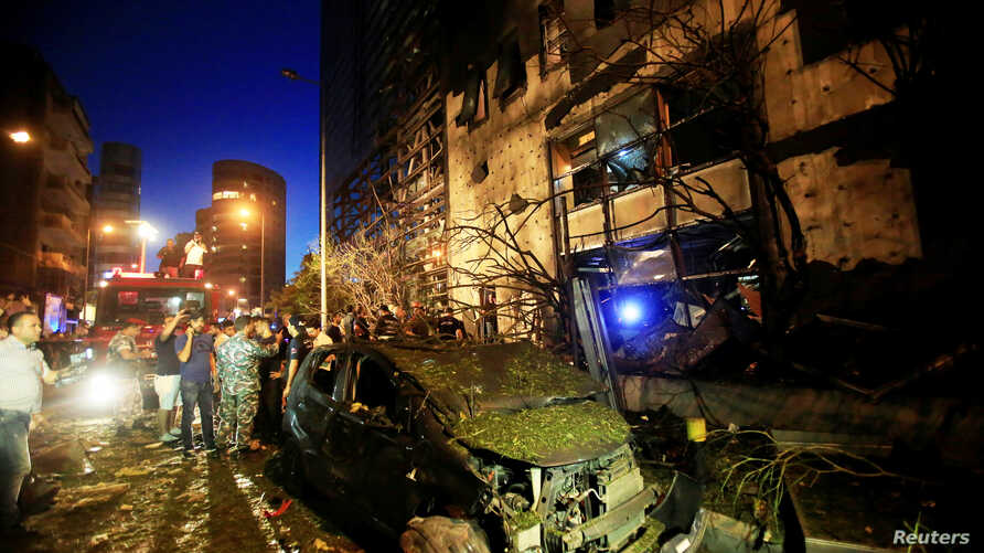 A wrecked vehicle is seen as policemen and civilians inspect the site of an explosion at Blom Bank in Beirut, Lebanon, June 12, 2016.