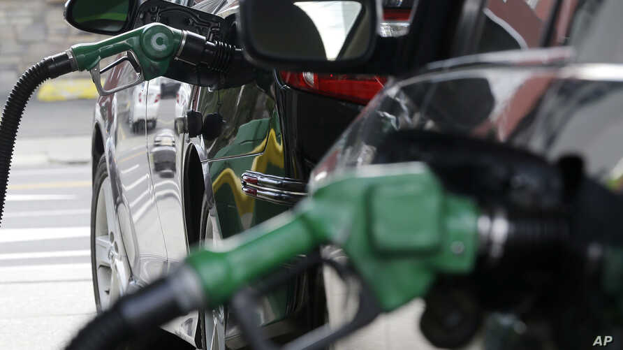 FILE - Gas is pumped into vehicles at a BP gas station in Hoboken, New Jersey, June 30, 2016.