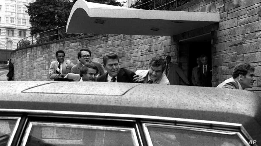 FILE - In this March 30, 1981, photo, U.S. president Ronald Reagan, center, is shown being shoved into his limousine by secret service agents after being shot outside a Washington hotel. The man who shot Reagan is scheduled to leave a Washington ment...
