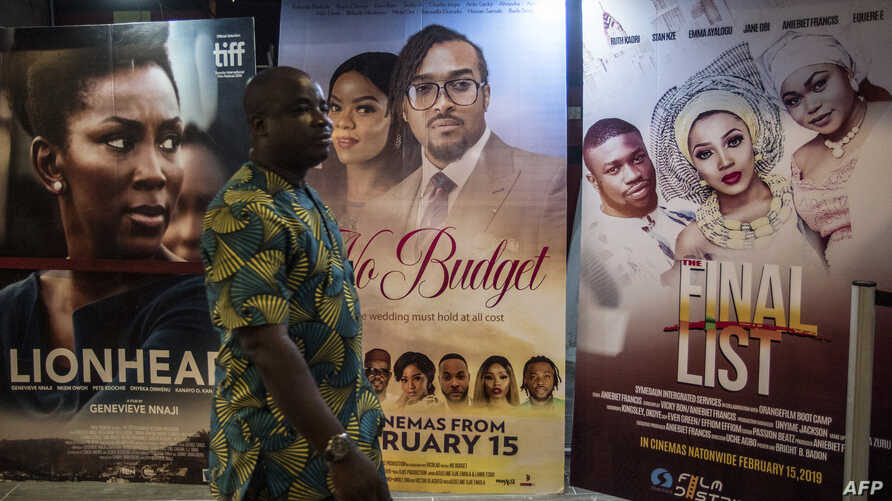 A man passes by Nigerian movie billboards at a cinema in Lagos, Feb. 19, 2019.