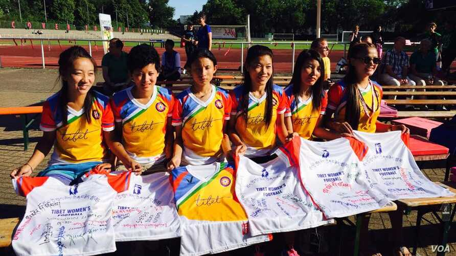 The Tibet Women's Soccer team signs autographs on jerseys, in Berlin, Germany, for the Discover Football event, June 30, 2015.