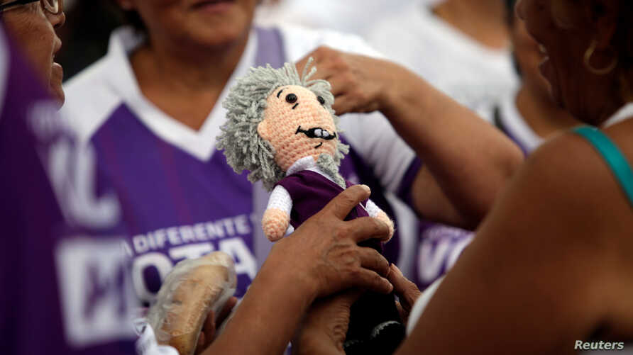 Supporters of Mexican presidential candidate Andres Manuel Lopez Obrador hold a doll resembling him, while gathering at the country's largest soccer stadium for his closing campaign rally, in Mexico City, June 27, 2018.
