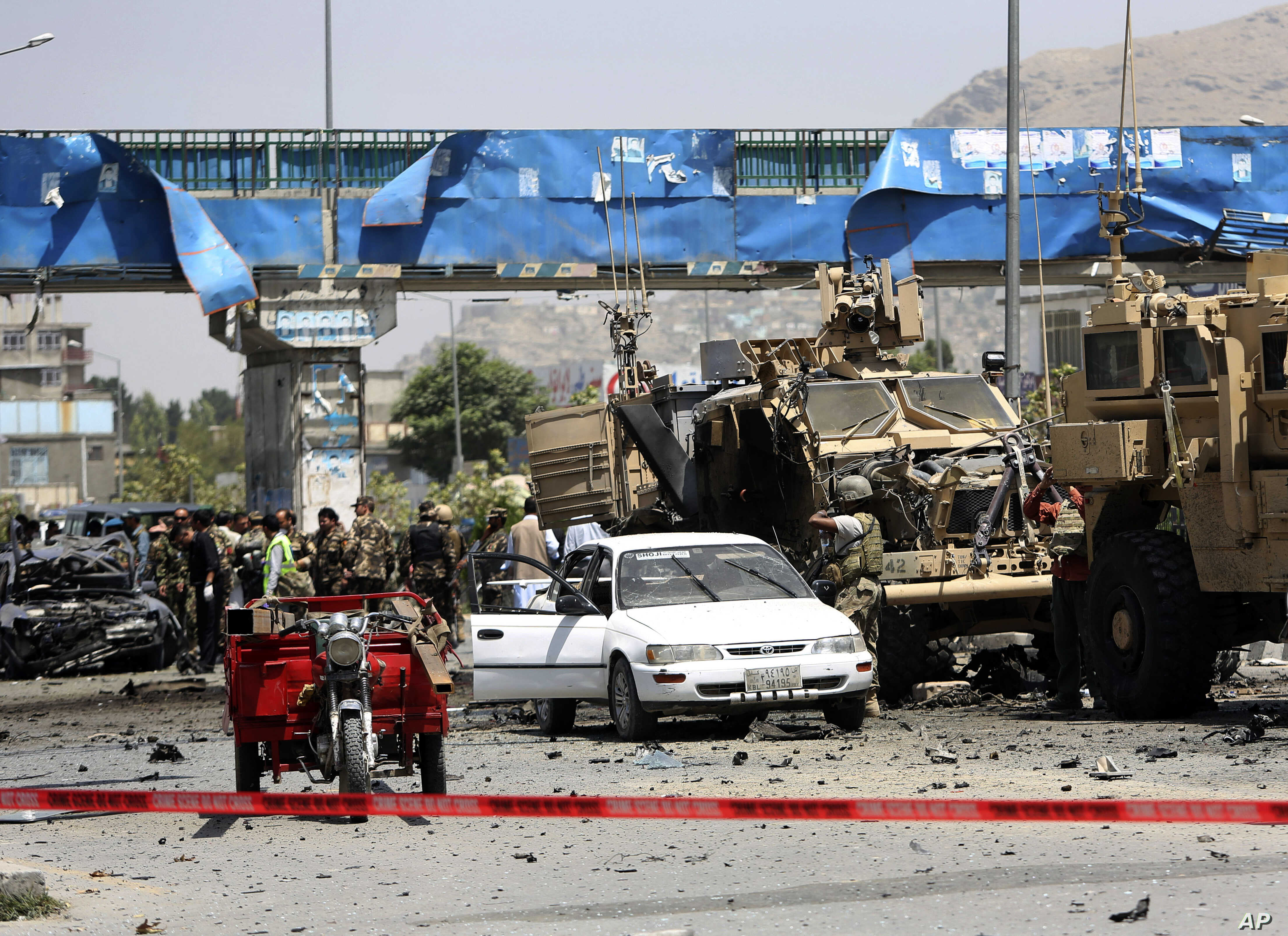 NATO and Afghan security forces inspect the site of a suicide attack in Kabul, Afghanistan, Aug. 10, 2014.