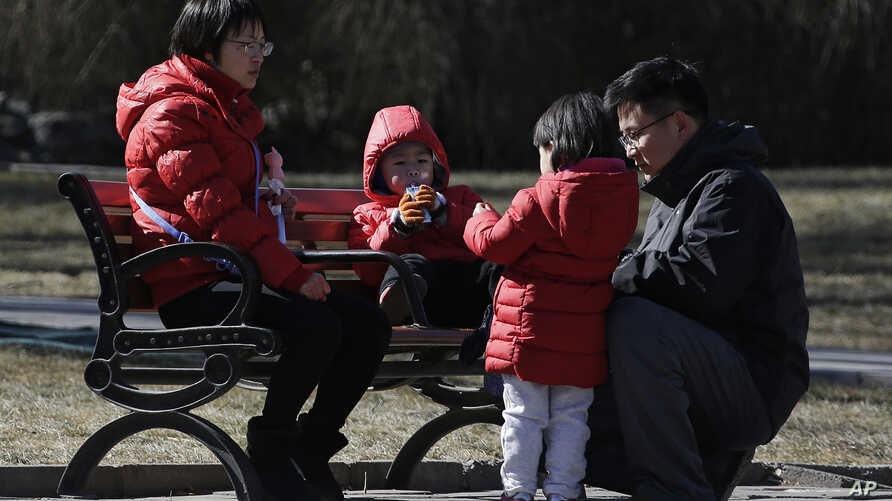 In this Feb. 17, 2019, photo, a couple spend time with their children at a park in Beijing. Facing a future demographic crisis and aging society, China's leaders are desperately seeking to persuade couples to have more children.