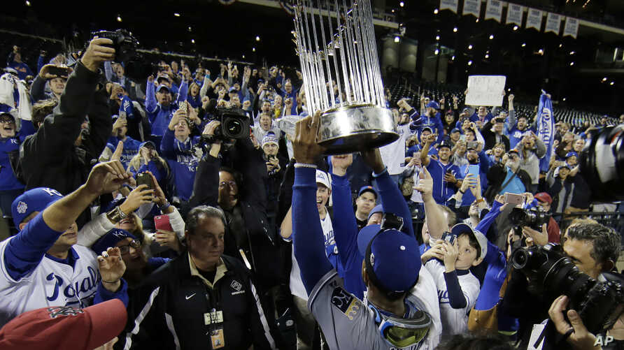 Kansas City Royals' Jarrod Dyson holds the World Series trophy after Game 5 of the Major League Baseball World Series against the New York Mets Monday, Nov. 2, 2015.
