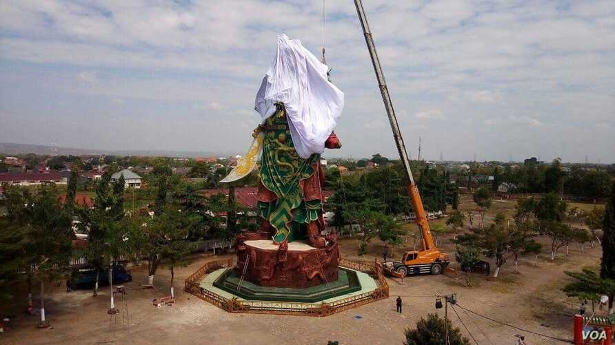 Workers cover at the statue in Tuban, East Java,  of the Chinese warrior god known variously as Kwan Sing Tee Koen, Kwan Kong, Kuan-Ti or Guan-Yu.