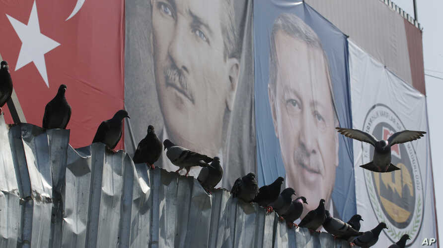 Posters of Mustafa Kemal Ataturk (L) founder of modern Turkey, and current President Recep Tayyip Erdogan are displayed at the Spice Bazaar plaza, during the re-opening ceremony following its restoration in Istanbul, May 4, 2018.