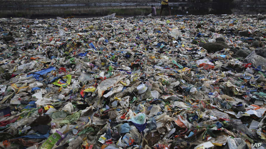 A man walks on the shores the Arabian Sea, littered with plastic and other garbage in Mumbai, India, June 4, 2018.