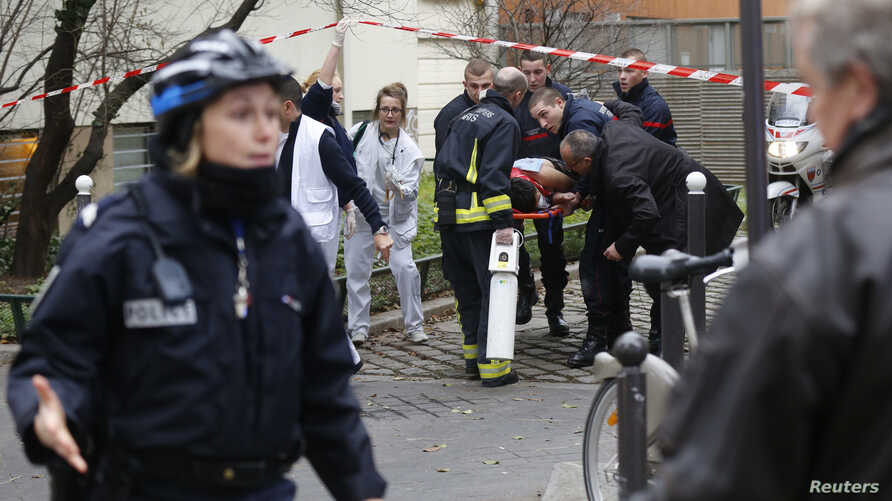 Firefighters carry a victim on a stretcher at the scene after a shooting at the Paris offices of Charlie Hebdo, a satirical newspaper, Jan. 7, 2015.