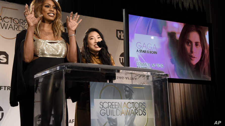 "Presenters Laverne Cox, left, and Awkwafina announce Lady Gaga as a nominee for outstanding performance by a female actor in a leading role for ""A Star is Born"" as Cox gives the Little Monsters monster claw hand gesture during the nominations announc"