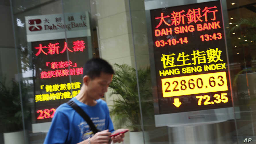 An electronic sign shows Hong Kong's benchmark Hang Seng stock index down just over 72 points by mid morning, Friday, Oct. 3, 2014.