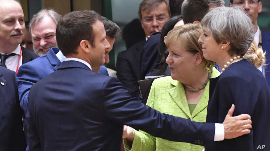 French President Emmanuel Macron (left) puts his hand on the shoulder of British Prime Minister Theresa May during a round table meeting at an EU summit in Brussels, June 22, 2017.
