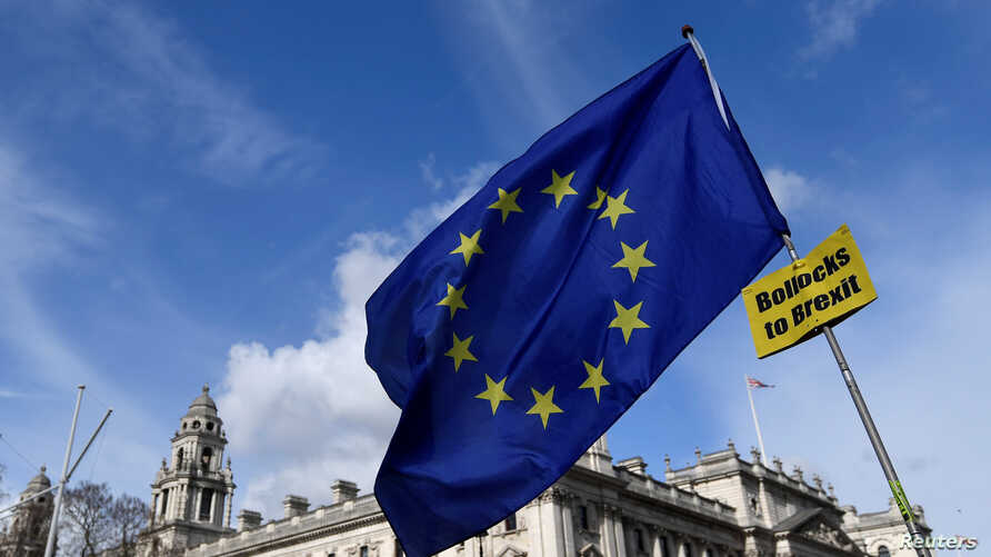 An anti-Brexit placard and EU flag are held aloft outside of the Houses of Parliament, in London, Britain, March 18, 2019.