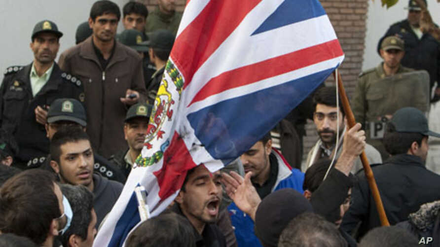 Protesters remove the flag of the British embassy in Tehran, November 29, 2011.