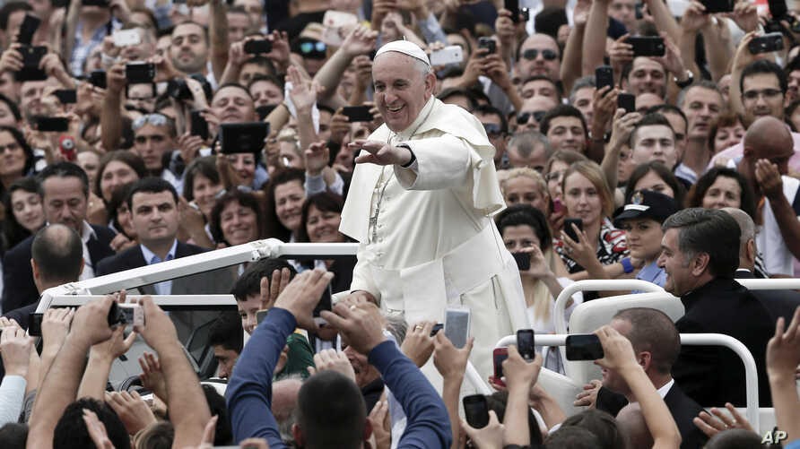 Pope Francis waves to faithful as he is driven through the crowd, in Mother Teresa Square, in Tirana, Sunday, Sept. 21, 2014.