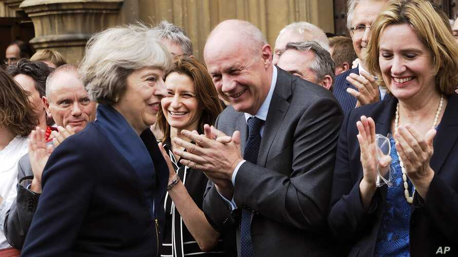 Britain's Theresa May is applauded by Conservative Party members of parliament outside the Houses of Parliament in London, July 11, 2016.