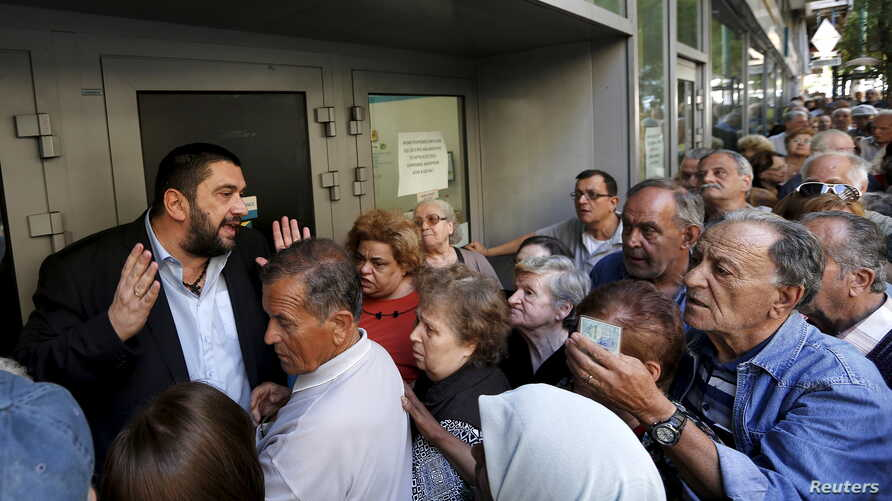 A bank manager tries to explain the situation to hundreds of pensioners queuing outside a National Bank branch in Athens, Greece, July 1, 2015. About one thousand Bank branches around Greece opened on Wednesday to allow pensioners to receive a small