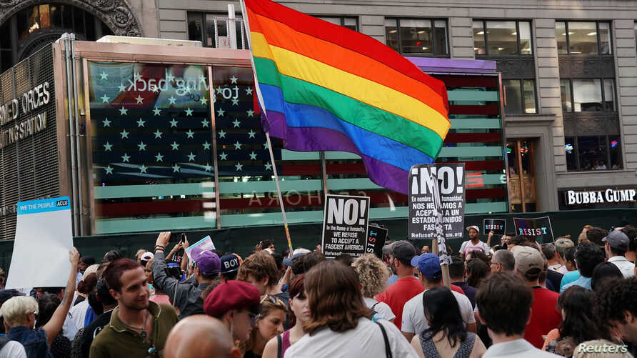 A rainbow flag flies as people protest U.S. President Donald Trump's announcement that he plans to reinstate a ban on transgender individuals from serving in any capacity in the U.S. military, in Times Square, in New York City, New York,  July 26, 20