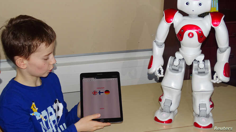 FILE - Daniel Connell uses a language-trainer robot, Elias, during his lesson at the school in Tampere, Finland, March 27, 2017.