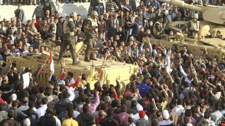 Armed soldiers look down on protesters surrounding military vehicles in Tahrir Square in Cairo, Egypt, February 2, 2011