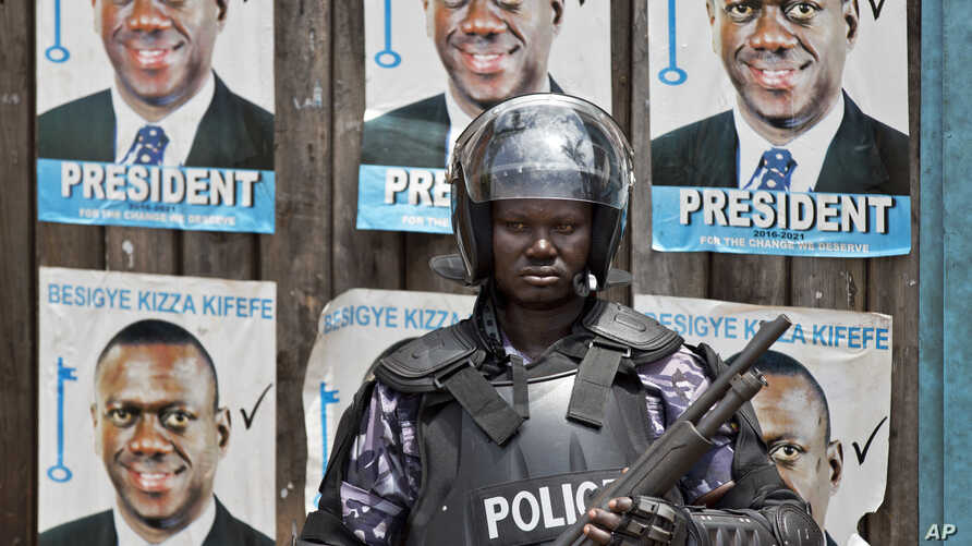 A Ugandan riot policeman blocks the gate of the party headquarters of opposition leader Kizza Besigye, shortly after raiding the premises for the second time in a week, in the capital Kampala, Uganda, Feb. 22, 2016.