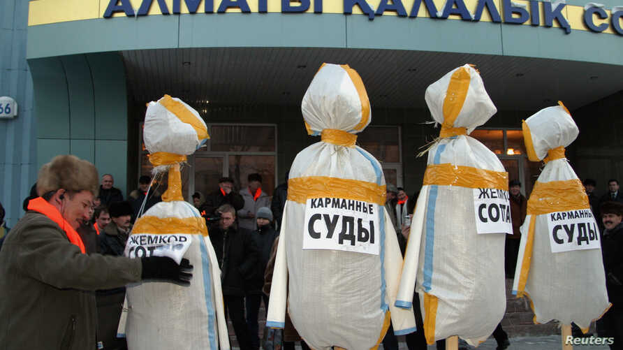 FILE - A supporter of Kazakhstan's opposition Democratic Choice of Kazakhstan sets up dummies of judges in front of a court building in Almaty, Feb. 9, 2005.