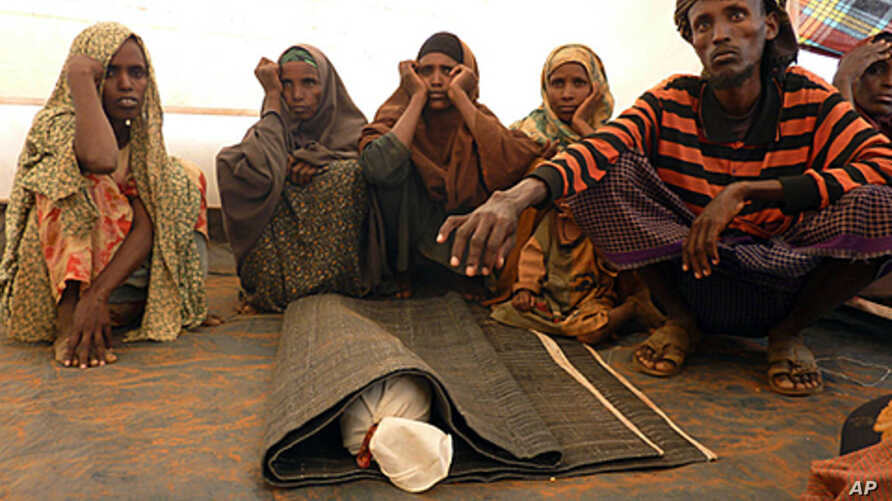 Somali refugee Mohamed Ibrahim (R) prepares to bury his son Sahro Mohamed, 1, who died of malnutrition in Ethiopia's Kobe camp, August 13, 2011