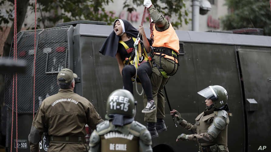 An activist dressed as a nun is lowered down by a police officers, and detained, after she and other protesters placed a pro-abortion banner above a road near Pope Francis' expected route, before the pontiff's arrival in Santiago, Chile, Monday, Jan.