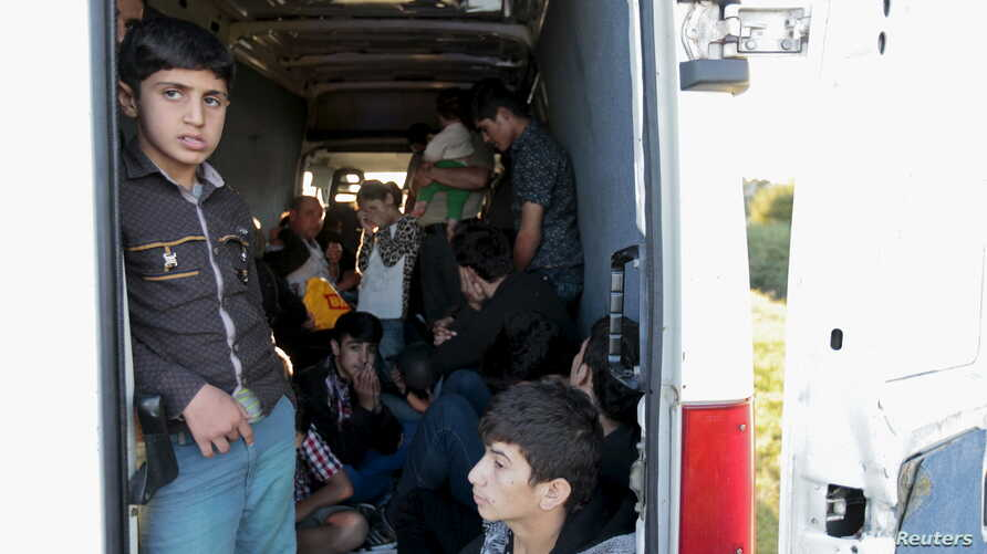 FILE - Migrants sit inside a van after being pulled over by police on the highway near Gyor, Hungary, Sept. 6, 2015.