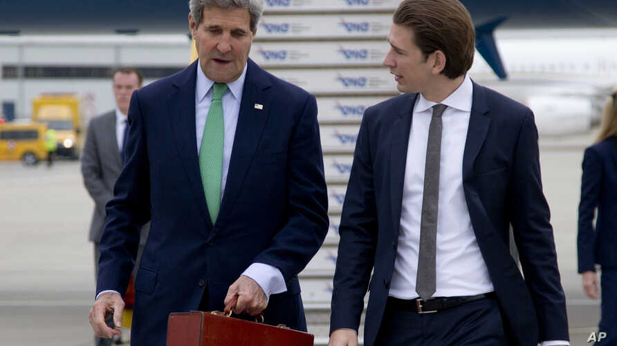 U.S. Secretary of State John Kerry, left, walks to his car with Austria's Foreign Minister Sebastian Kurz, right, as he arrives at Vienna International Airport, in Vienna, Austria, Oct. 15, 2014.
