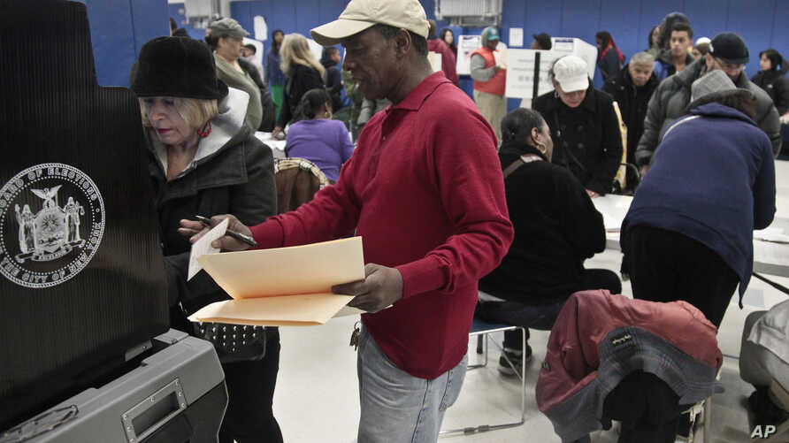 A poll worker assists a voter arriving from a relocated polling site that closed after flooding from superstorm Sandy on Manhattan's lower east side in New York, November 6, 2012.