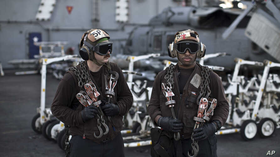 APTOPIX Islamic State US Carrier Photo EssayIn this Thursday, Sept. 10, 2015 photo, U.S. Navy air wing plane captains carry chains as they pause on the flight deck of the USS Theodore Roosevelt aircraft carrier.