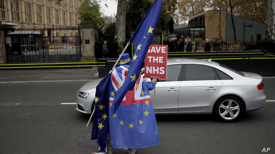 Anti-Brexit supporter Steve Bray from south Wales runs after a car carrying former UK Independence Party leader Nigel Farage outside the Houses of Parliament in London, Nov. 15, 2018. Two British Cabinet ministers, including Brexit Secretary Dominic