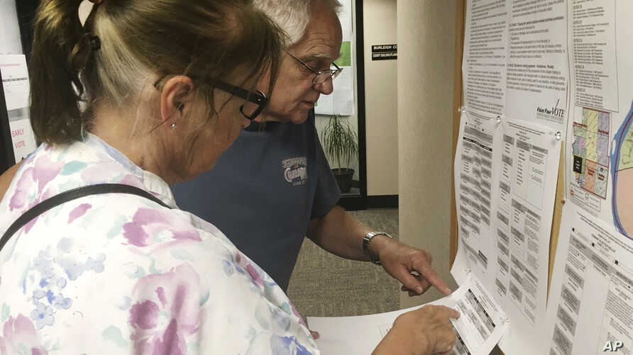 FILE - Dave and Jane Will inspect a sample ballot in Bismarck, N.D., June 5, 2018.