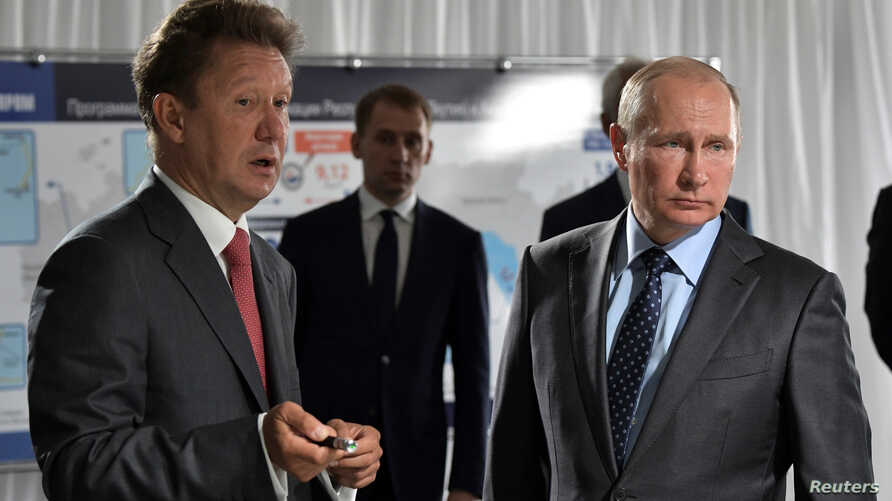 FILE - Russian President Vladimir Putin listens to Gazprom Chief Executive Alexei Miller during a visit to a construction site of the Gazprom's Amur gas processing plant near the far eastern town of Svobodny, in Amur region, Russia, Aug. 3, 2017.