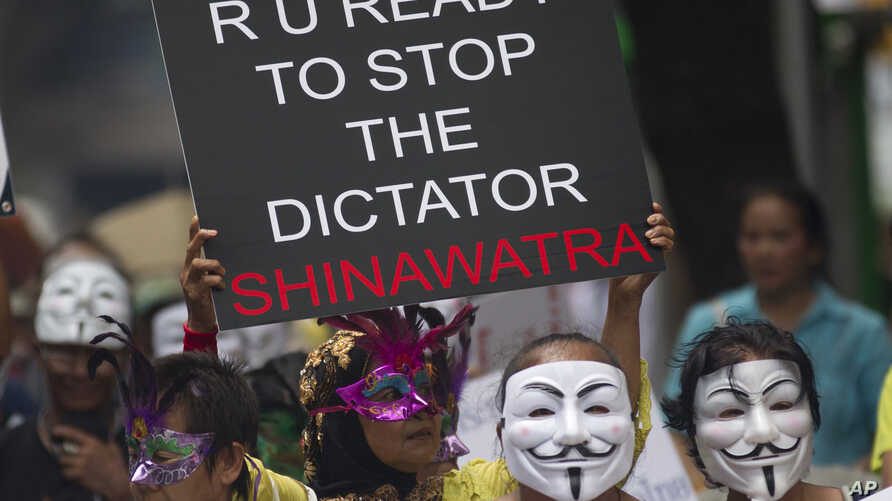 Masked Thai protesters holding placards and banners stage an anti-government rally  in Bangkok, May 31, 2013.