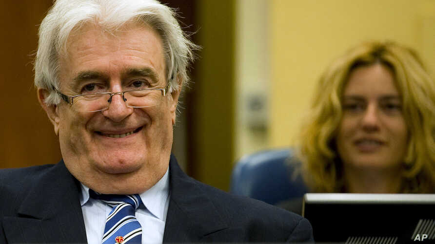 Suspected war criminal and former Bosnian Serb leader Radovan Karadzic smiles as he takes his seat on the defense bench in a courtroom to start his defense at the U.N. war crimes tribunal in The Hague, Netherlands, Oct. 16, 2012.
