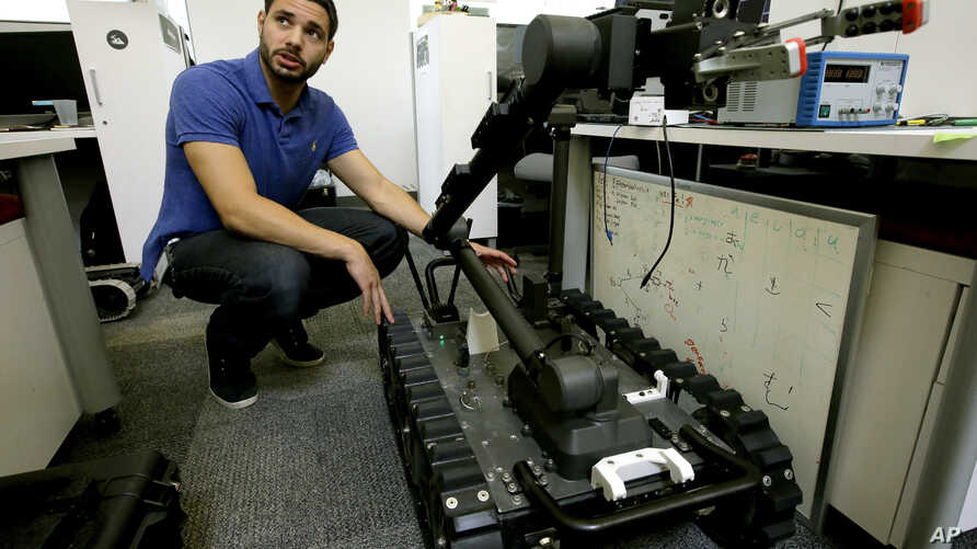 FILE - Software engineer Nicholas Otero speaks with a colleague about features on a Centaur robot, right, at Endeavor Robotics in Chelmsford, Massachusetts, Aug. 28, 2018.