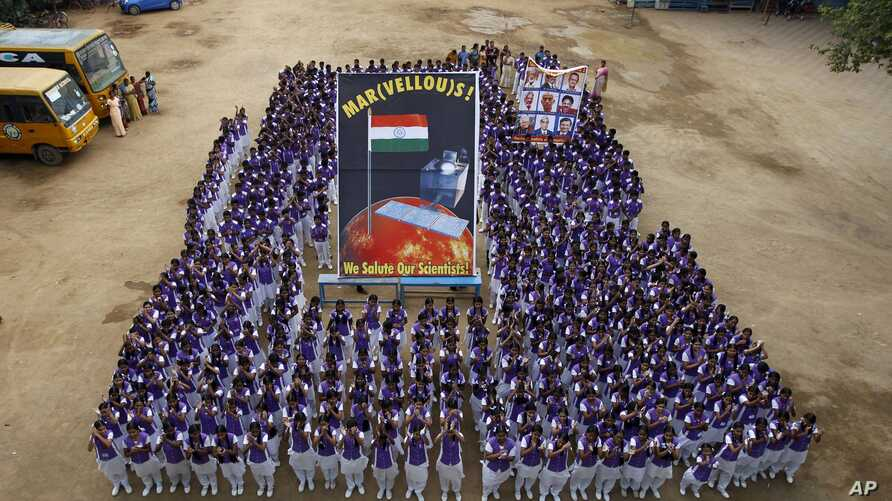 Indian school children pose for photographs with a poster of Mars Orbiter Mission satellite as they celebrate its success in Chennai, India, Sept. 24, 2014.