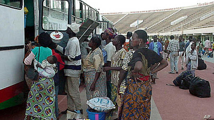 Part of millions of frightened immigrants, some Burkina Faso citizens unload their belongings at the national soccer stadium in Ouagadougou, Burkina Faso after they came home from the cocoa plantations and coffee fields of neighboring Ivory Coast (Fi
