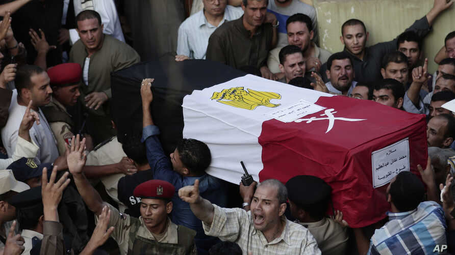 FILE - Egyptians carry the coffin of 1st Lt. Mohammed Adel Abdel Azeem, killed in an attack by Islamic militants in the Sinai, during the funeral procession at his home village of Tant Al Jazeera in Qalubiyah, north of Cairo, July 2, 2015.