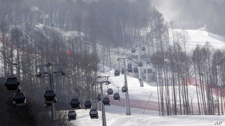 FILE - In this Jan. 22, 2016, file photo, gondolas make their way through a thinned forest up the ski slope which would be the venue for the Pyeongchang 2018 Winter Olympics at the Jeongseon Alpine Center in Jeongseon, South Korea.