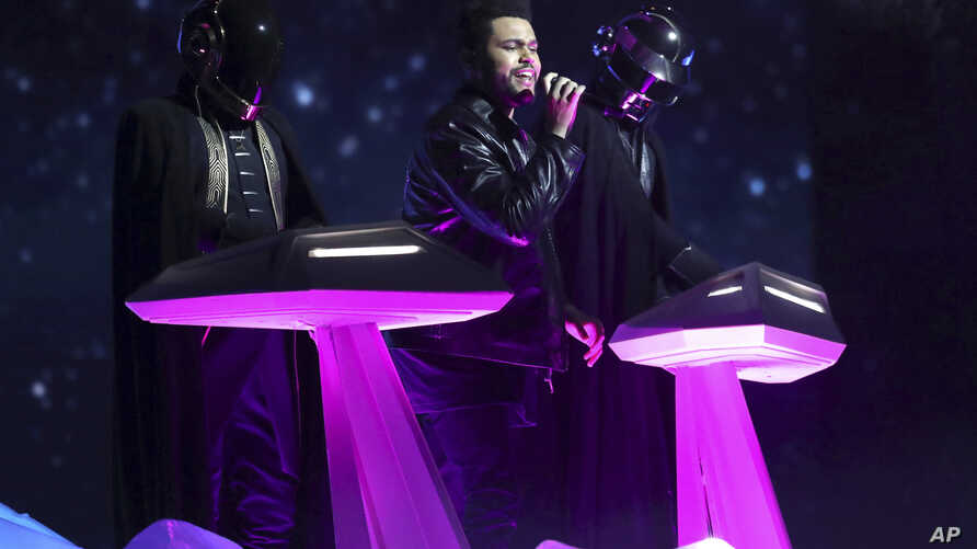 The Weeknd, center, and Daft Punk perform at the 59th annual Grammy Awards, Feb. 12, 2017.