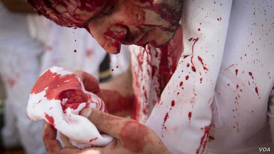 Often done with a knife stroke to the head, the act of bloodletting is called tatbir. (J. Owens/VOA)