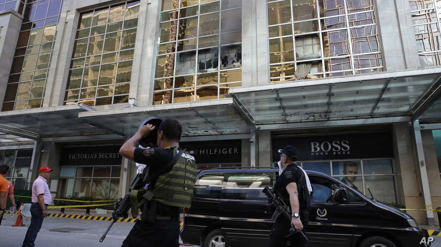 Policemen walk past a still smoldering part of a hotel at the Resorts World Manila complex, early June 2, 2017, in Manila, Philippines.
